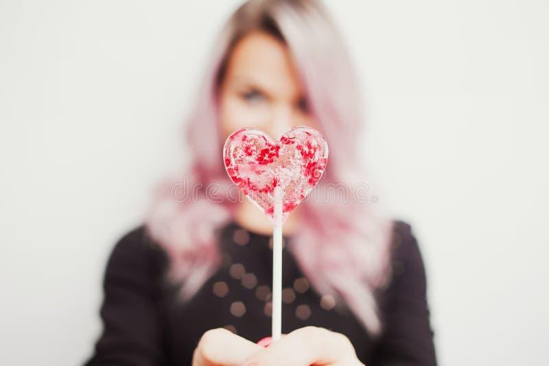 有一个棒棒糖的可爱的迷人的女孩以心脏的形式 一年轻女人的画象有桃红色头发和桃红色糖果的 免版税图库摄影