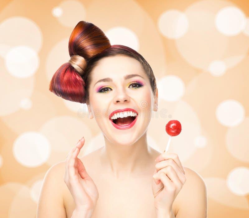 有一个棒棒糖的美丽的微笑的妇女在起泡的背景 免版税图库摄影