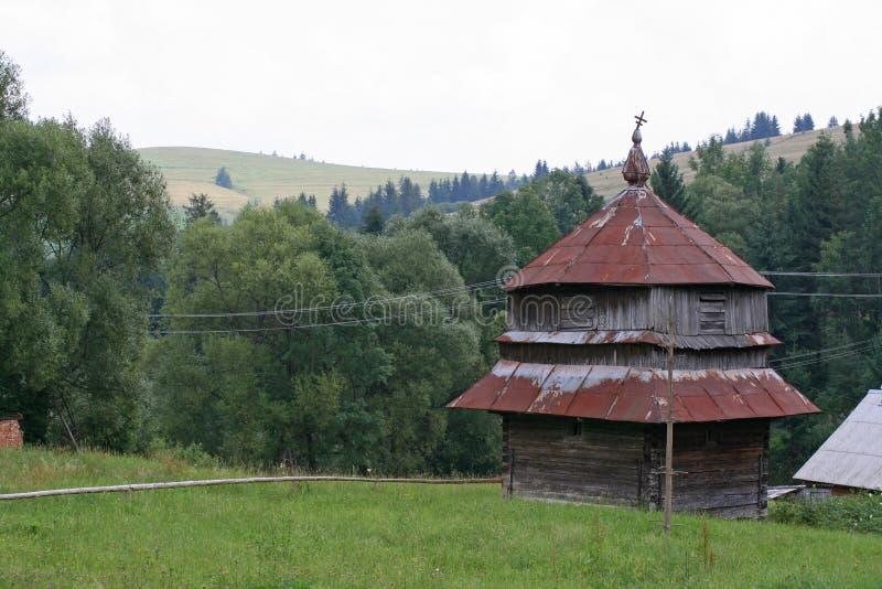 有一个棕色屋顶的老木教会在横过喀尔巴阡山脉 库存照片