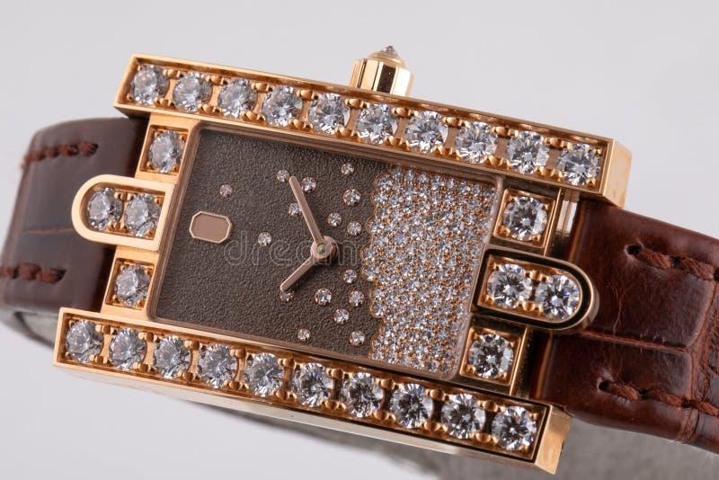 有一个棕色拨号盘的女性金黄手表有顺时针方向石头的,棕色,构筑石头,与棕色皮带 免版税库存图片
