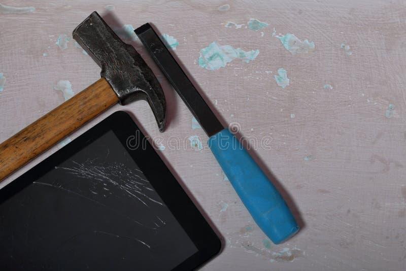 有一个残破的屏幕的片剂说谎与破旧的油漆的表面上 附近锤子和凿子 库存照片