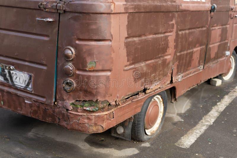 有一个泄了气的轮胎的一辆老生锈的小巴在城市街道上站立 免版税库存照片