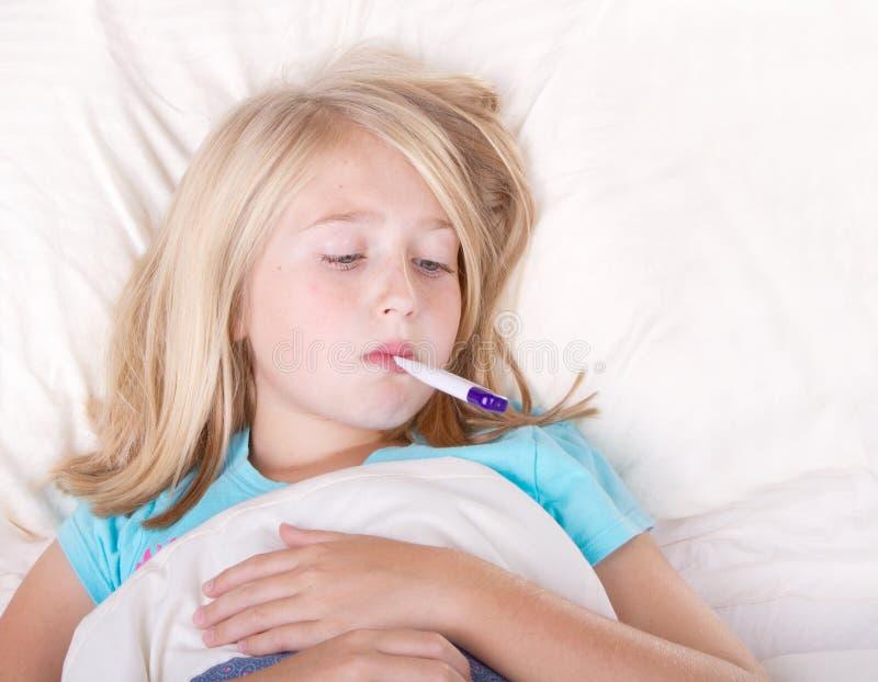 有一个温度计的病的女孩在嘴 库存照片