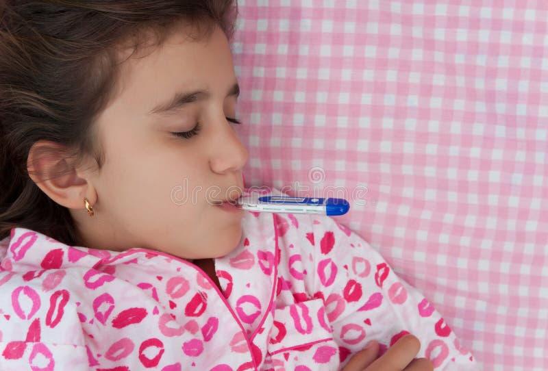 有一个温度计的病的西班牙女孩在她的嘴 库存图片