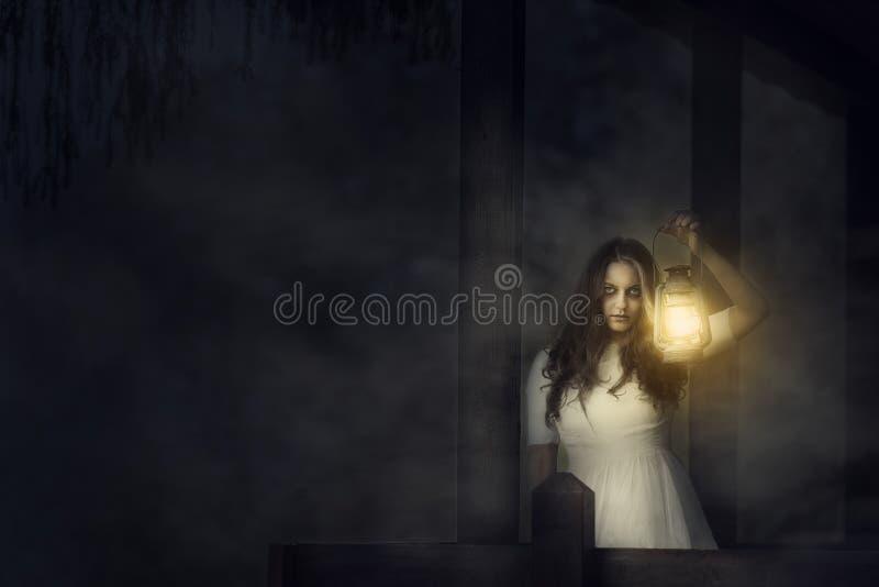 有一个灯笼的可怕妇女在夜场面 免版税库存图片