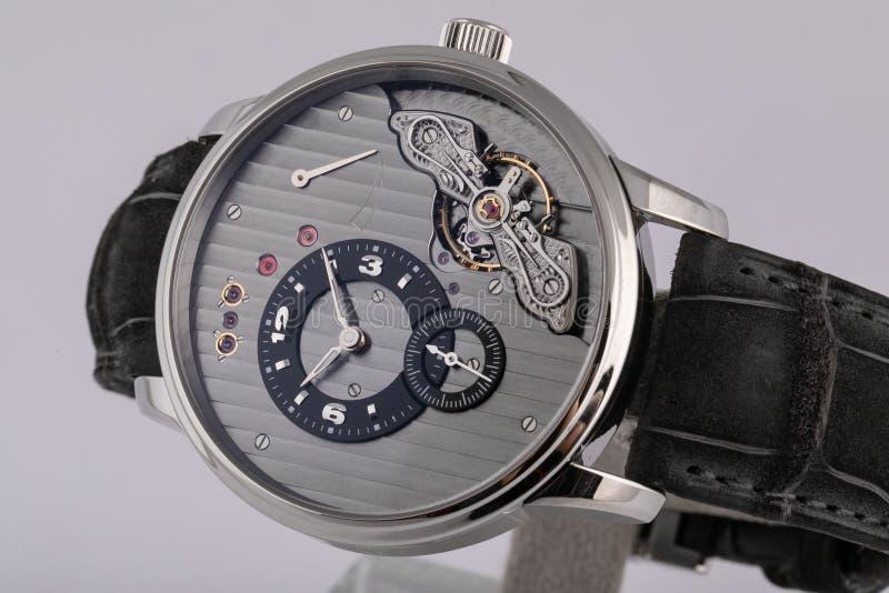有一个灰色拨号盘的精神银色手表,银色顺时针,秒表,当黑皮带,被隔绝在白色背景 库存图片