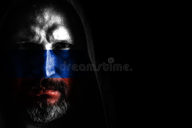 有一个灰色胡子的残酷人在有锋利的阴影的敞篷在黑背景 r 库存图片