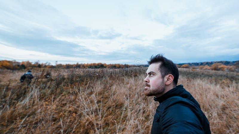 有一个狂躁表示的人在黑夹克偷偷靠近秋天恶化的秋天森林概念的受害者  图库摄影