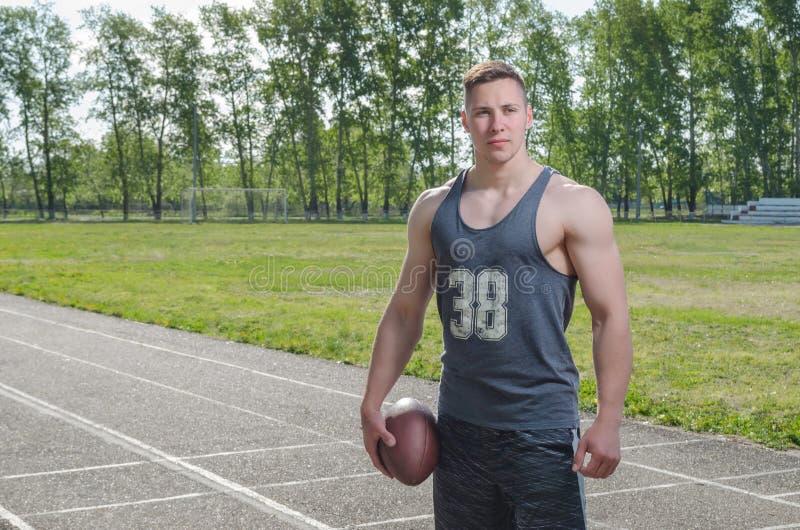 有一个球的年轻肌肉四分卫在体育场 免版税图库摄影