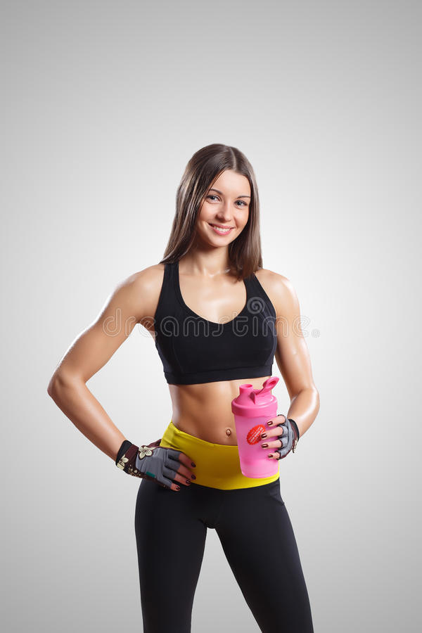 有一个瓶的一个女孩在健身房 库存图片