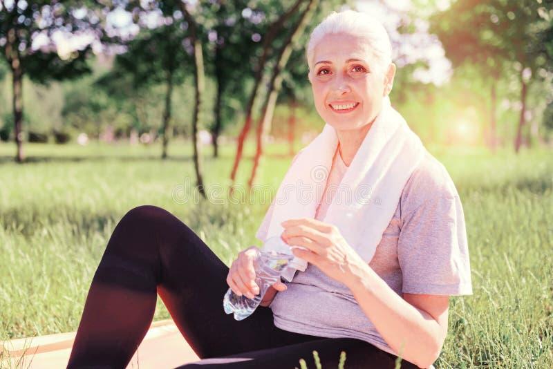 有一个瓶的微笑的年长妇女水 免版税库存照片