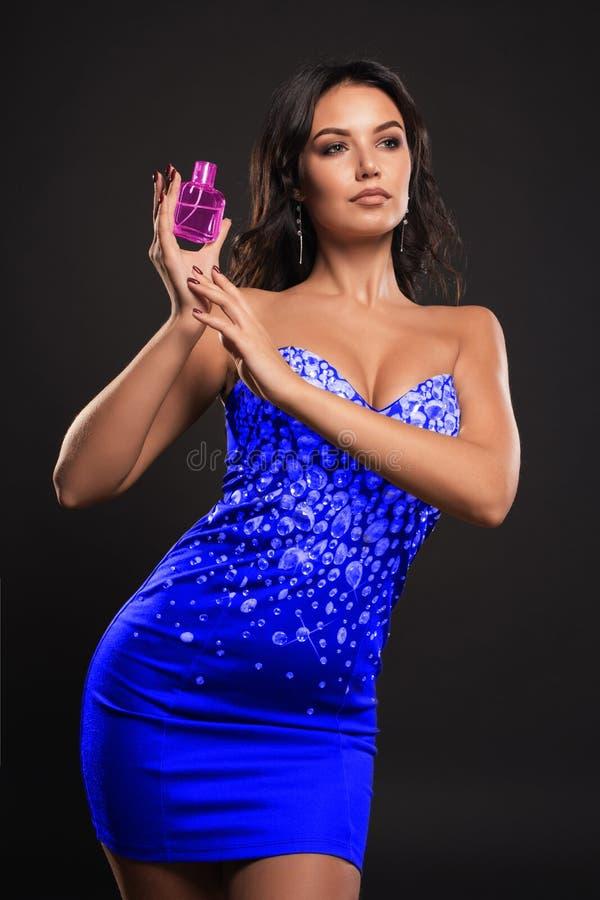 有一个瓶的豪华女孩香水在手上在黑暗的背景 免版税库存照片