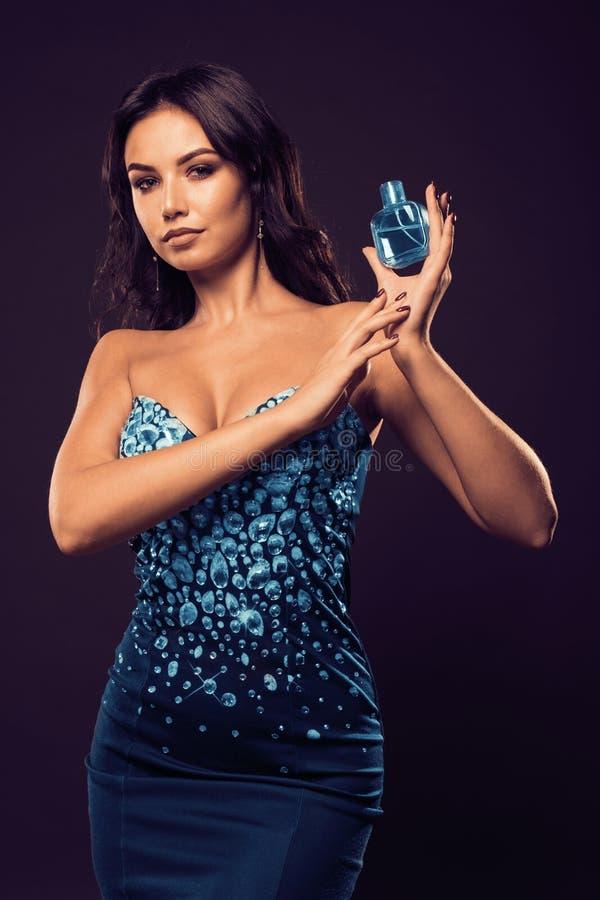 有一个瓶的豪华女孩香水在手上在黑暗的背景 库存图片