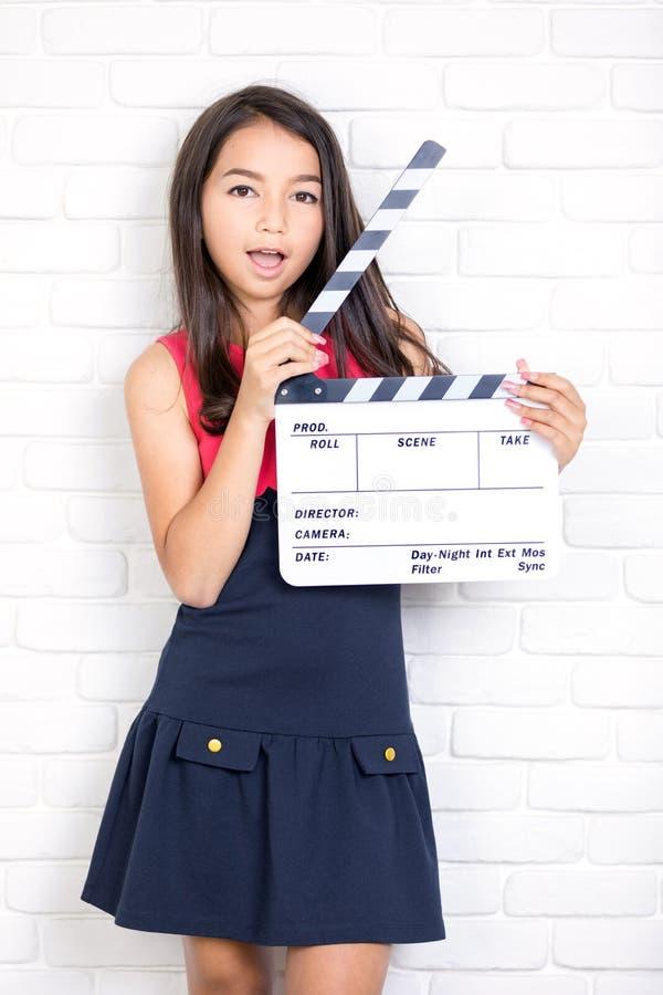有一个电影拍板的女孩在白色砖墙背景 库存照片
