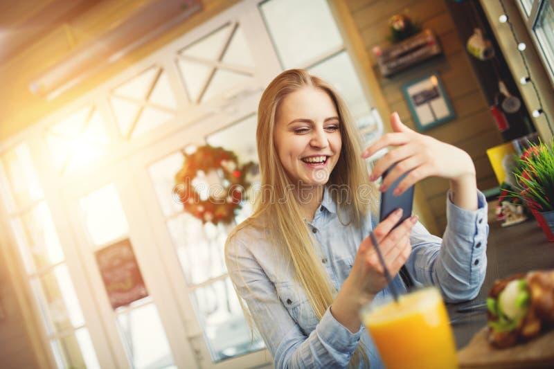 有一个电话的女孩在她的休息在与圣诞节装饰的一个时髦咖啡馆的手上 免版税图库摄影