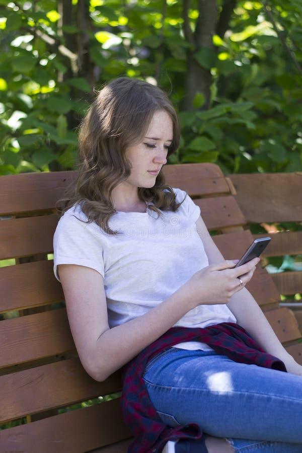 有一个电话的女孩在长凳 免版税库存图片