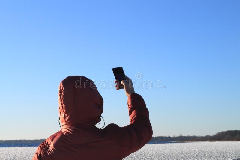 有一个电话的年轻人在他的手上 免版税库存照片