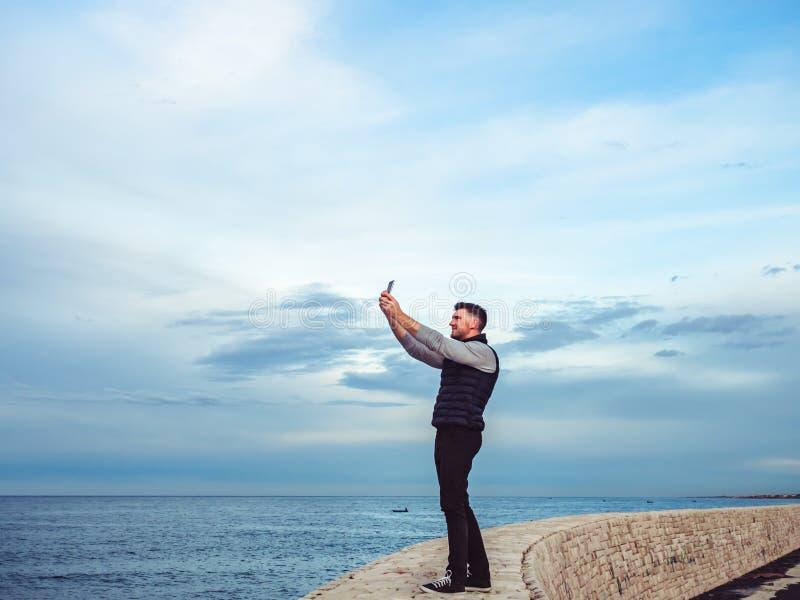 有一个电话的时兴,可爱的人在海背景  库存照片