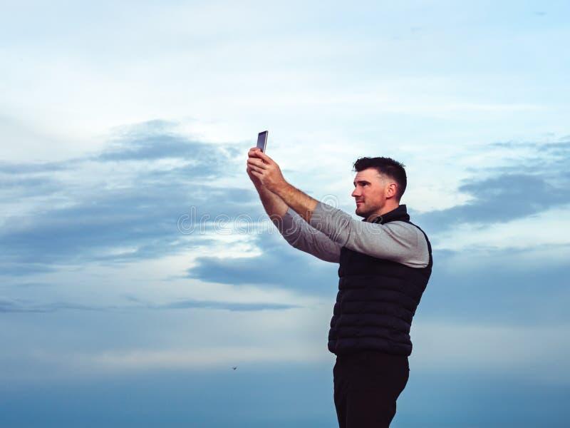 有一个电话的时兴,可爱的人在海背景  免版税库存照片