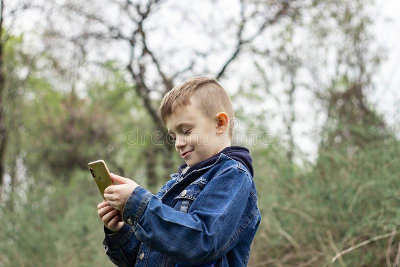 有一个电话的男孩在公园 免版税图库摄影
