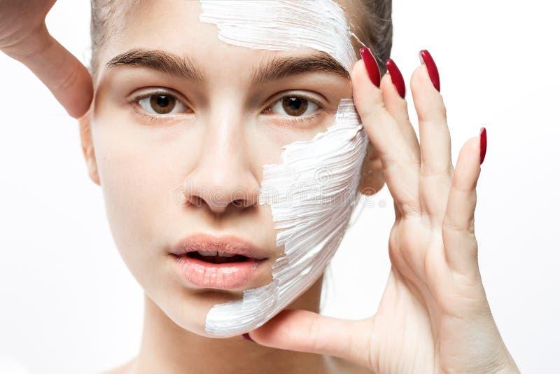 有一个白色化妆面具的年轻女人在一半她的面孔握她的手在她的在白色背景的面孔 库存图片
