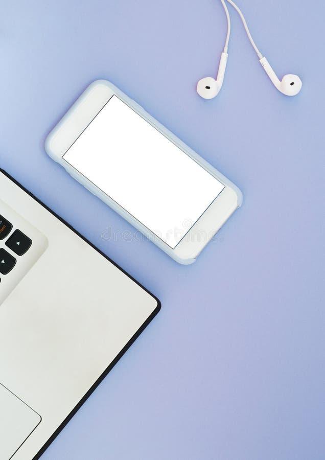 有一个白色屏幕、一台膝上型计算机和耳机的一个电话在蓝色背景 平的位置小配件和地方文本的 免版税图库摄影
