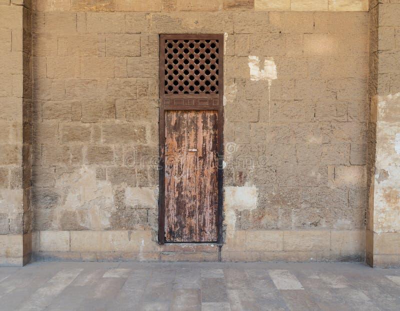 有一个的老被放弃的石砖墙风化了木门和木栅格窗口,老开罗,埃及 免版税库存照片