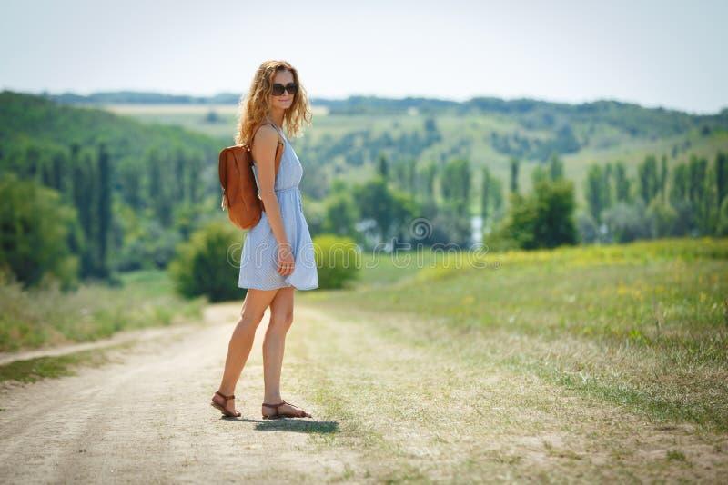 欧美农村淫妇_有一个皮革背包的少妇在夏天农村路. 室外, 幸福.