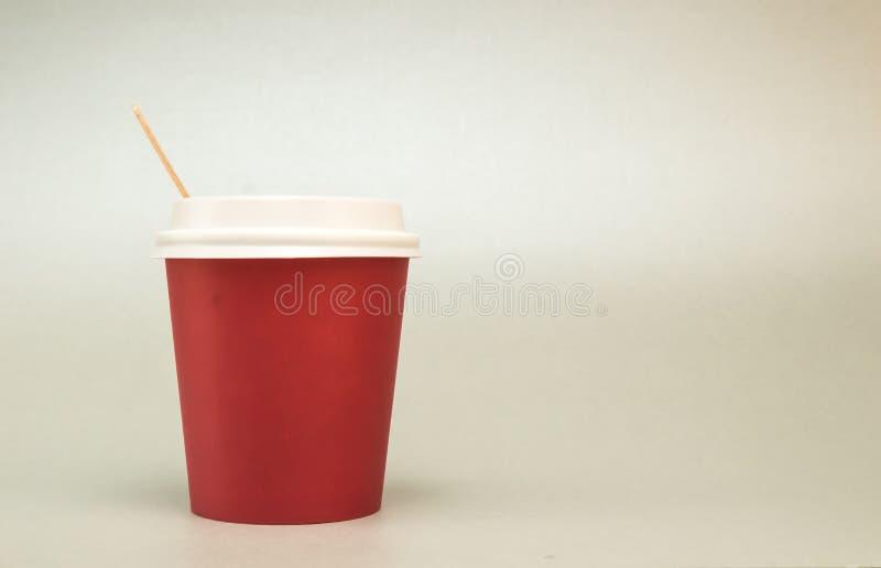 有一个盒盖的红色纸杯在白色背景的咖啡立场的,在它旁边是木咖啡匙 库存照片