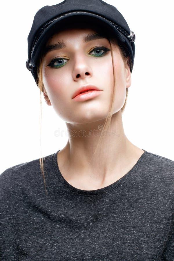 有一个盖帽的一个女孩在她的头和t恤杉 与柔和的光亮的构成的美好的模图片