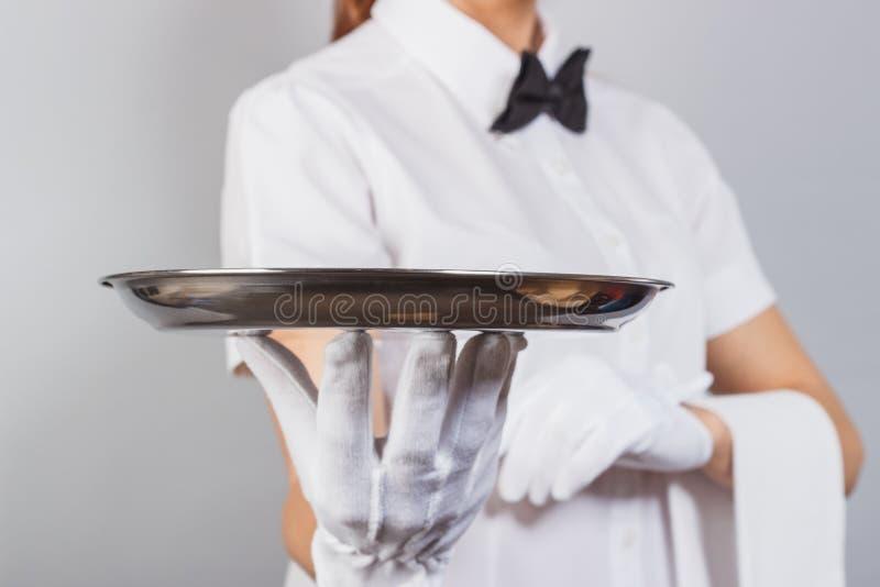 有一个盘子的妇女女服务员在手上 免版税库存照片