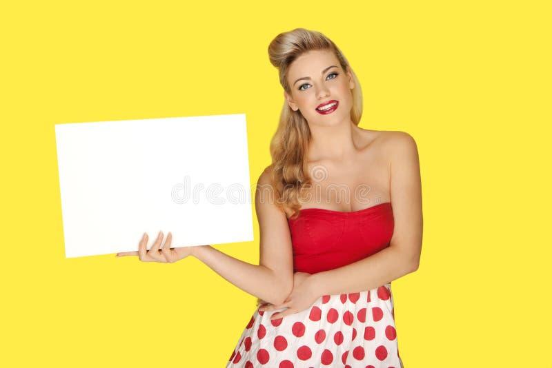 有一个空白符号的迷人的白肤金发的妇女 库存图片