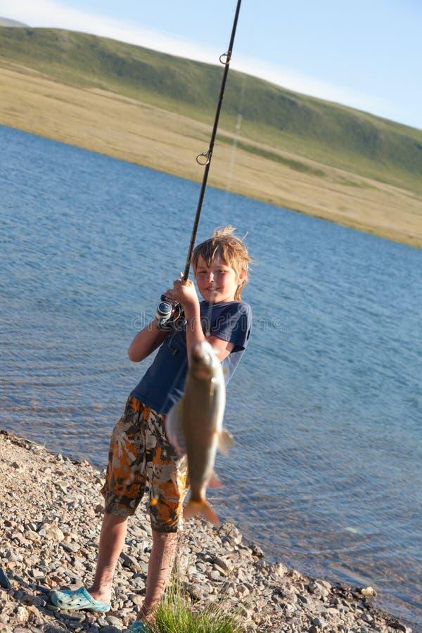 有一个空转的抓住河鳟的男孩 免版税库存照片