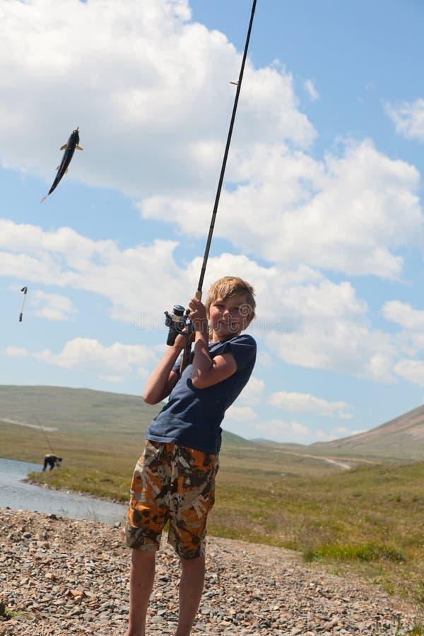 有一个空转的抓住河鳟的男孩 库存图片