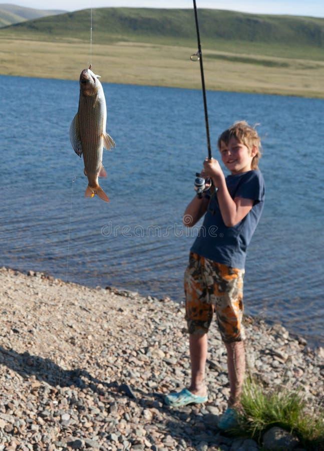 有一个空转的抓住河鳟的男孩 免版税库存图片