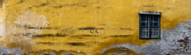 有一个窗口的被破坏的黄色房子墙壁 库存图片