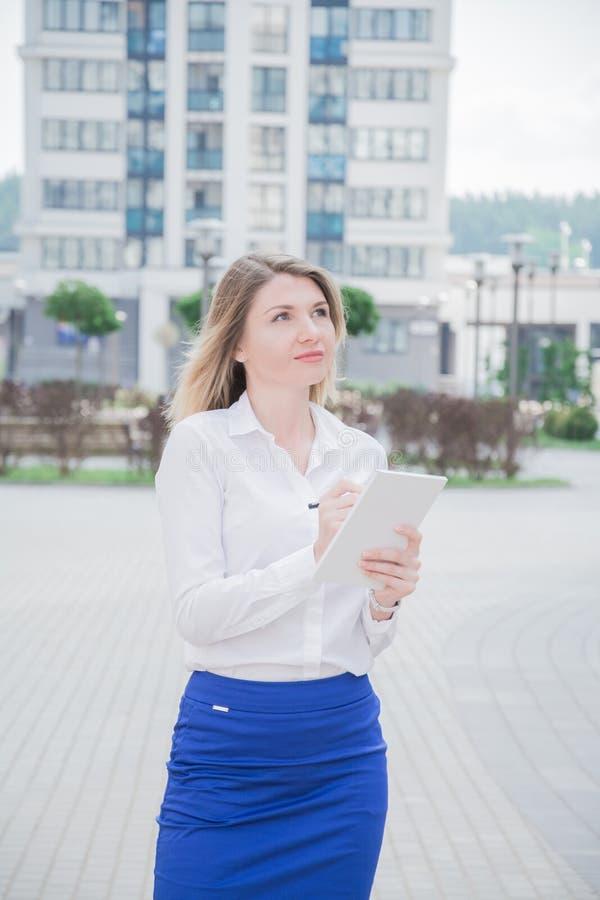 有一个笔记本的地产商女孩在她的手上检查现代住宅区 库存图片