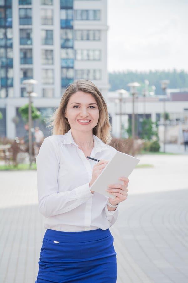 有一个笔记本的地产商女孩在她的手上检查现代住宅区 免版税库存图片