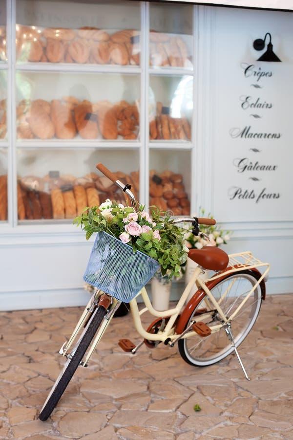 有一个篮子的葡萄酒黄色自行车与在面包店的咖啡馆附近花架以木蓝色房子为背景 S 免版税库存照片