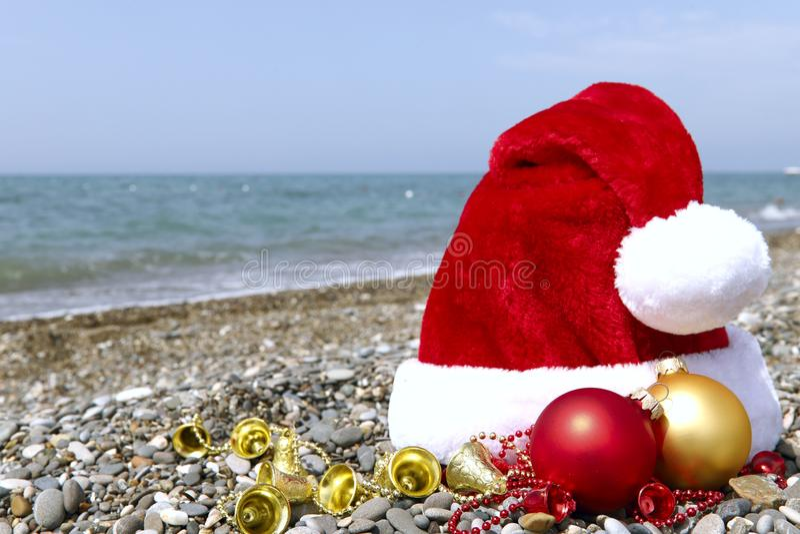 有一个红色和黄色球的圣诞老人帽子和在小卵石的黄色小珠以海为背景 库存照片