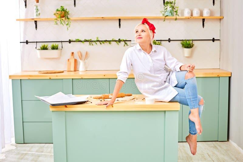 有一个红色头饰带的年轻金发碧眼的女人在白色衬衫坐厨房用桌用烘烤的面团 库存图片