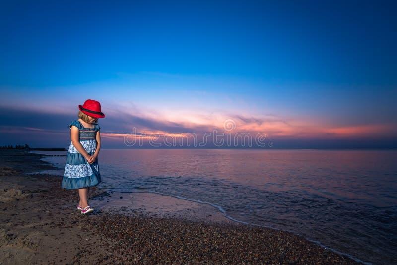 有一个红色帽子的女孩在日落的一个海滩 免版税图库摄影