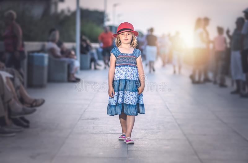 有一个红色帽子的女孩走在海边散步的 库存图片
