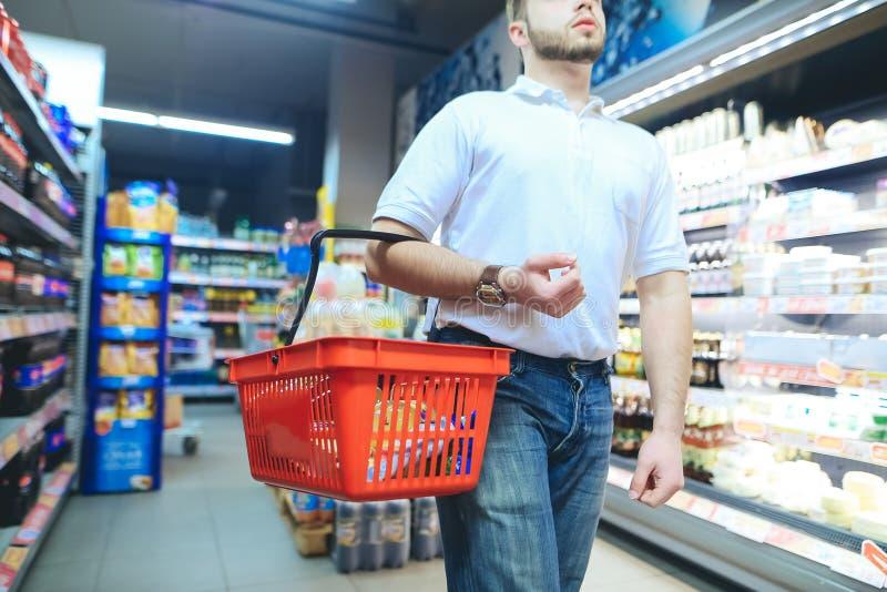 有一个红色手提篮的一个人在超级市场附近漫步 一个人在超级市场买物品 库存照片