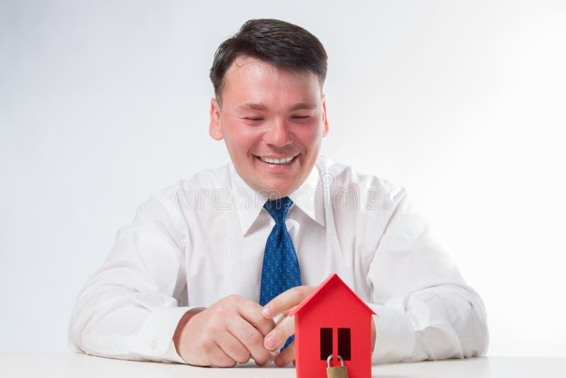 有一个红色纸房子的人 免版税库存图片