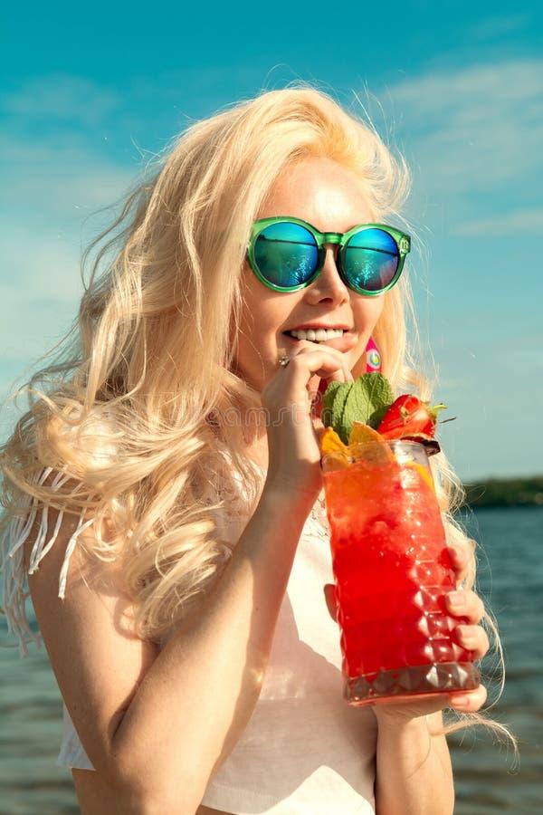 有一个红色美丽的鸡尾酒的美丽的白肤金发的女孩在她的由海/河的手上 免版税库存图片
