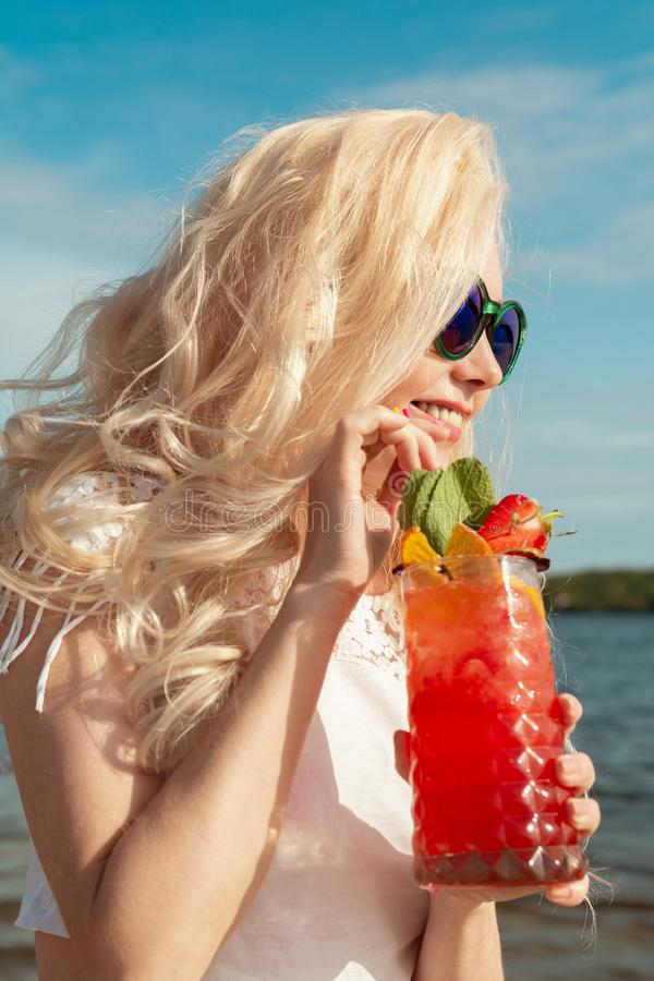 有一个红色美丽的鸡尾酒的美丽的白肤金发的女孩在她的由海/河的手上 库存照片