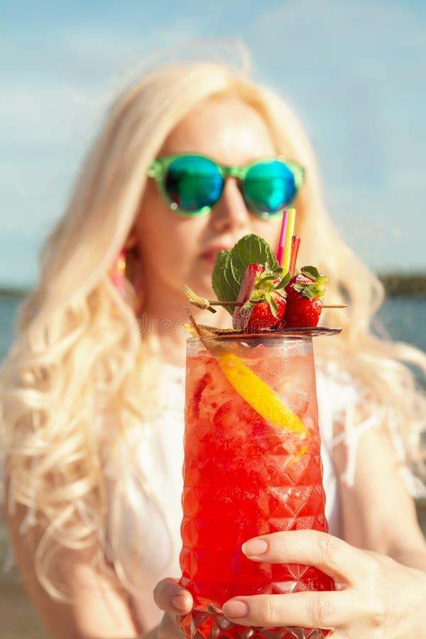 有一个红色美丽的鸡尾酒的美丽的白肤金发的女孩在她的由海/河的手上 免版税库存照片