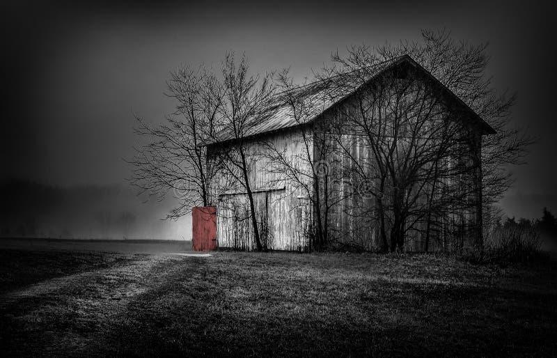 有一个红色门风景的老谷仓 免版税库存照片