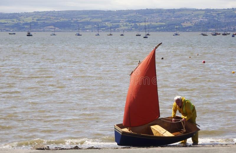 有一个红色风帆的一艘蓝色充气救生艇 免版税图库摄影